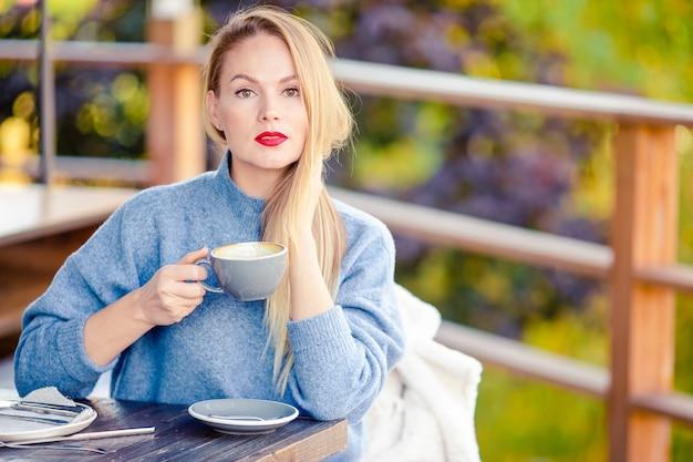 Mujer tomando café en el parque otoño