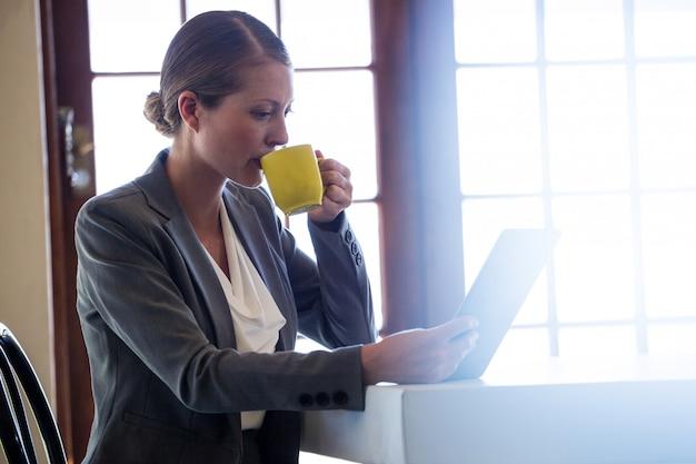 Mujer tomando café y usando tableta