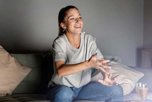 Mujer tomando cerveza y bocadillos en casa mientras ve la televisión