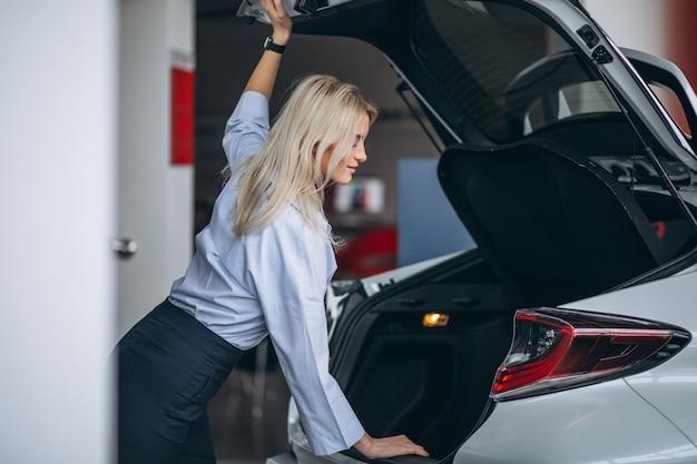 Mujer tomando la decisión de comprar un coche.