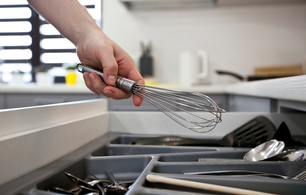 Mujer está tomando equipo de cocina de estante con utensilios de cocina