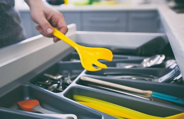 La mujer está tomando el equipo de cocina del estante con utensilios de cocina.