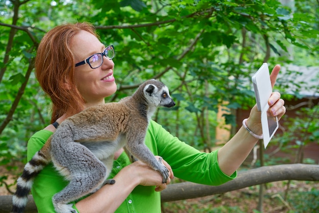 Mujer tomando foto autofoto con lemur de cola anillada