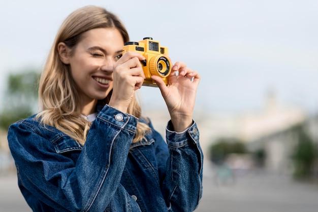 Mujer tomando una foto con cámara amarilla