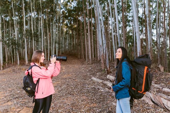 Mujer tomando foto de su amigo en el bosque
