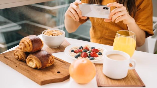 Mujer tomando foto de desayuno en mesa blanca