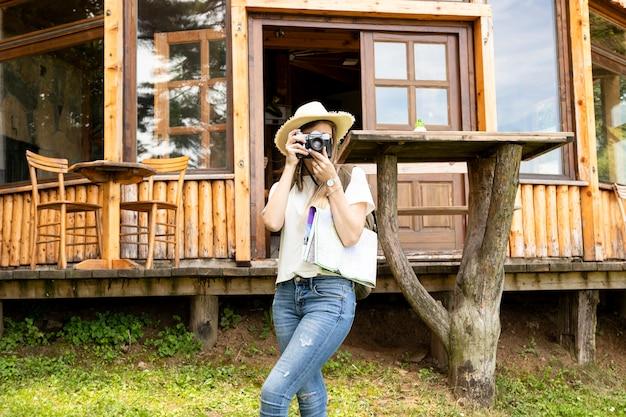 Mujer tomando una foto frente a una casa