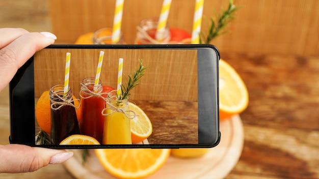Mujer tomando foto de jugo de frutas en su teléfono inteligente. la mano sostiene un teléfono con una foto. jugos de frutas en una brillante foto de verano. sin marcas y logotipos visibles