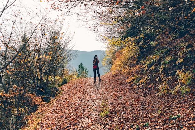 La mujer está tomando una foto del paisaje de la naturaleza mientras camina en la colina en otoño.