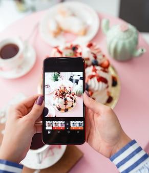 Mujer tomando una foto de pastelería con bayas en smartphone