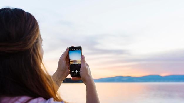 Mujer tomando una foto con el teléfono inteligente de la puesta del sol
