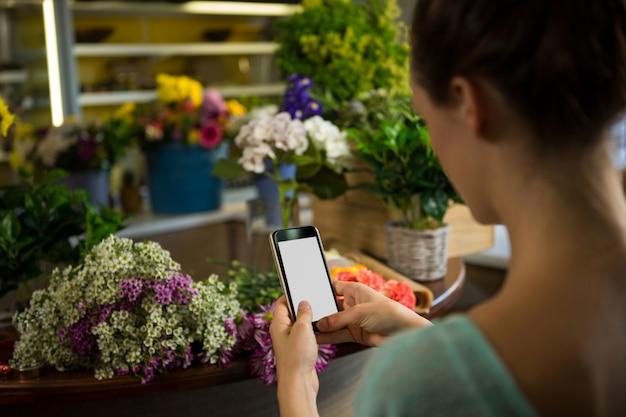 Mujer tomando fotografía de ramo de flores