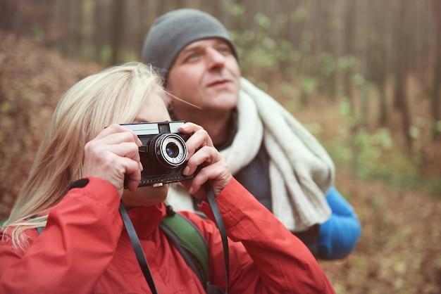 Mujer tomando fotografías en el bosque