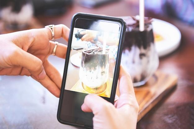 Mujer tomando fotos de bebida de cacao y pastel