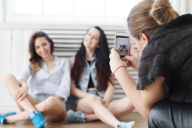 Mujer tomando fotos a dos mujeres sentadas en el suelo