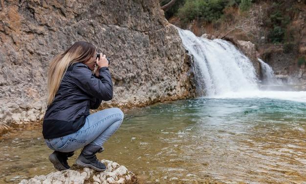 Mujer tomando fotos de la naturaleza