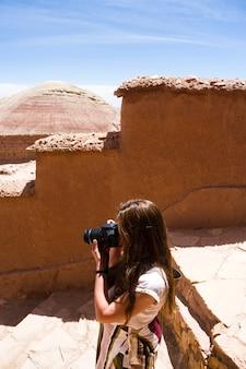 Mujer tomando fotos en las ruinas del desierto