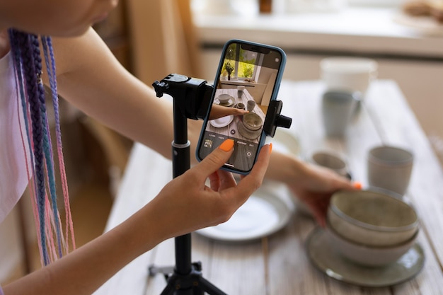 Mujer tomando fotos para su negocio con utensilios de cocina de cerámica