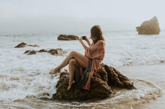 Mujer tomando fotos con su teléfono en la playa