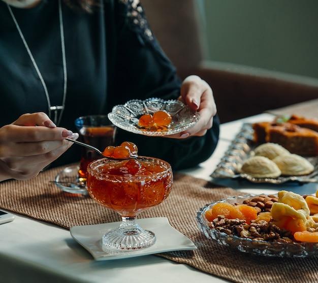 Mujer tomando mermelada de cerezas de la olla de cristal en el plato en la configuración de té