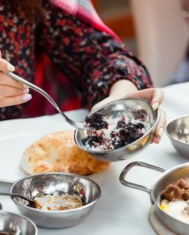 Mujer tomando mezcla de frambuesa y queso de tazón de acero