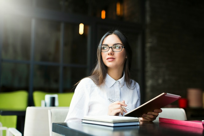 Mujer tomando notas en la cafetería