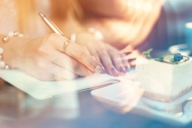 Mujer tomando notas mientras está sentado en una cafetería.