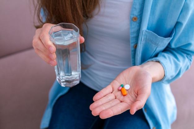 Mujer tomando pastillas y vitaminas para el bienestar. atención de salud y tratamiento de enfermedades.