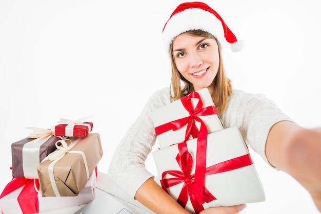 Mujer tomando selfie con cajas de regalo