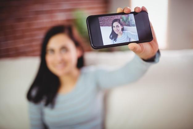 Mujer tomando selfie en casa