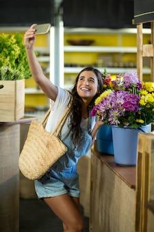 Mujer tomando un selfie en floristería