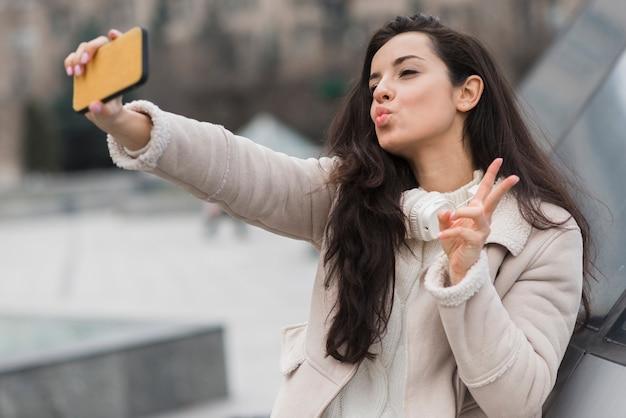 Mujer tomando selfie mientras hace el signo de paz