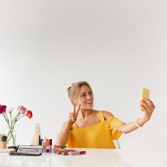 Mujer tomando selfie mientras muestra signo de paz