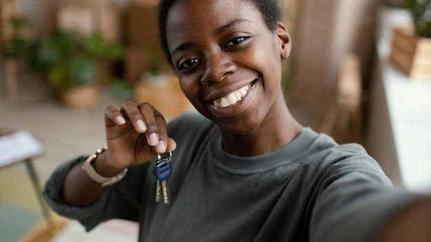 Mujer tomando selfie mientras sostiene las llaves de su nuevo hogar