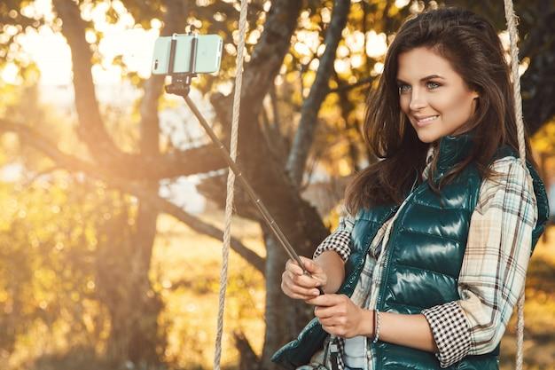 Mujer tomando selfie en el parque otoño