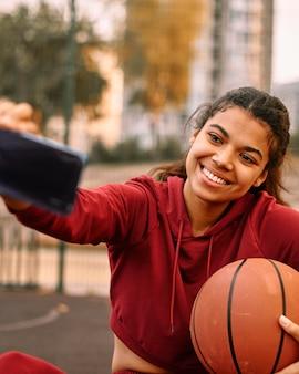 Mujer tomando un selfie con su baloncesto