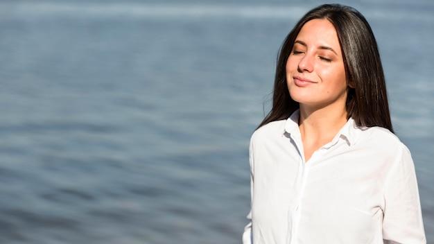 Mujer tomando el sol y la brisa de la playa con espacio de copia