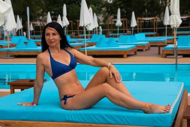 Una mujer está tomando el sol en la piscina. vacaciones de verano en la playa