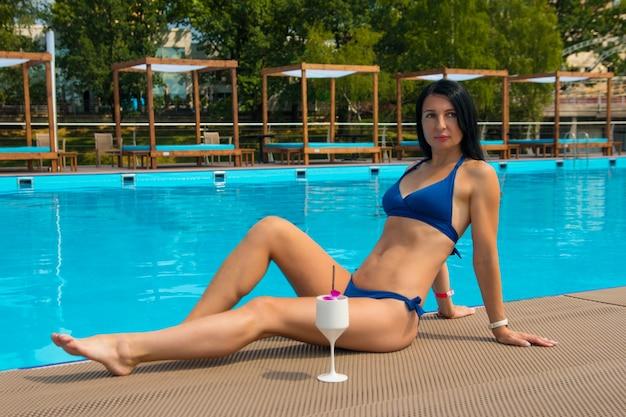 Una mujer está tomando el sol en la piscina.