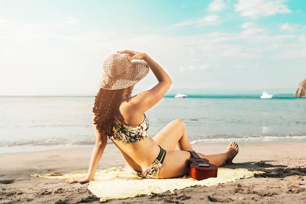 Mujer tomando el sol en la playa de arena