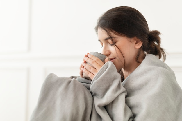Mujer tomando un sorbo de té de la taza durante el invierno