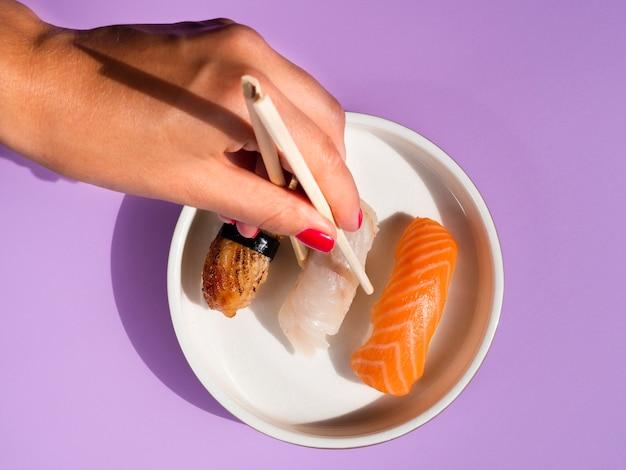 Mujer tomando un sushi de un plato blanco sobre fondo azul.
