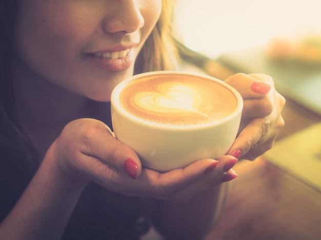 Mujer tomando una taza de café con un corazón dibujado en la espuma