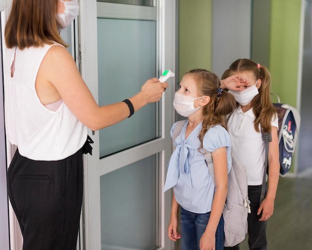 Mujer tomando la temperatura de los estudiantes