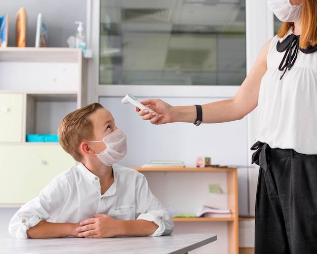Mujer tomando la temperatura de un niño en clase