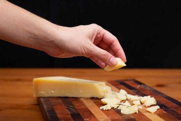 Mujer tomando trozo de parmesano de tablero de madera