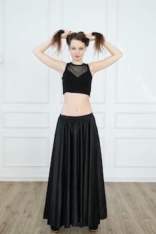 Mujer en top corto negro y falda larga poniendo sus pelos en updo