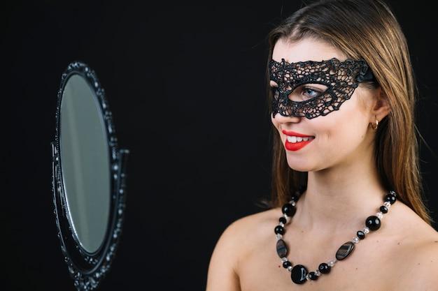 Mujer en topless sonriente en máscara de carnaval mirando en espejo de mano
