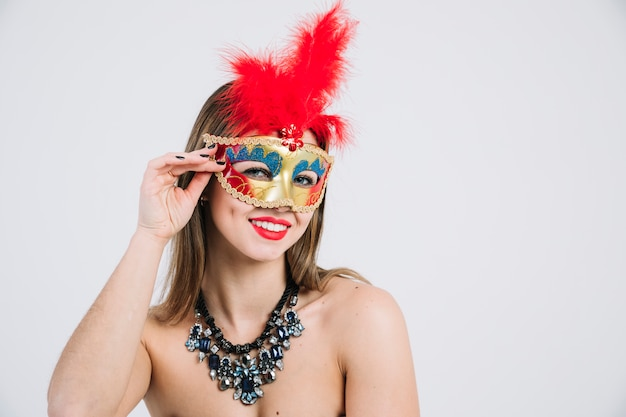 Mujer en topless sonriente con mascarada máscara de carnaval sobre fondo blanco