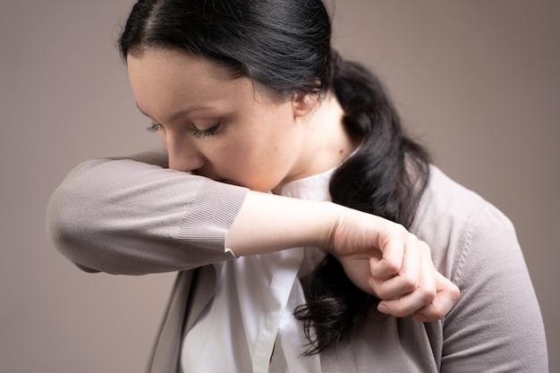 La mujer tose en el codo. prevención de coronavirus